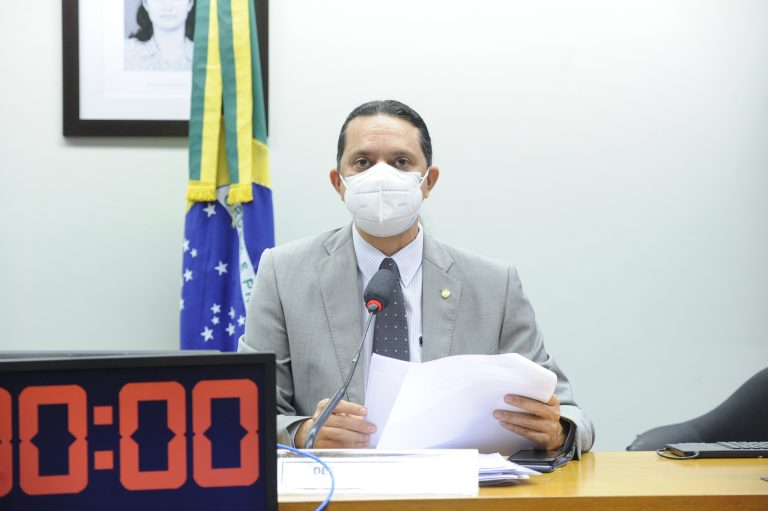 Deputado Weliton Prado usa máscara branca e está sentado com um papel nas mãos olhando para a frente