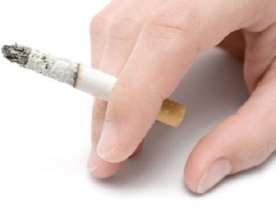 Uma mão segura um cigarro aceso