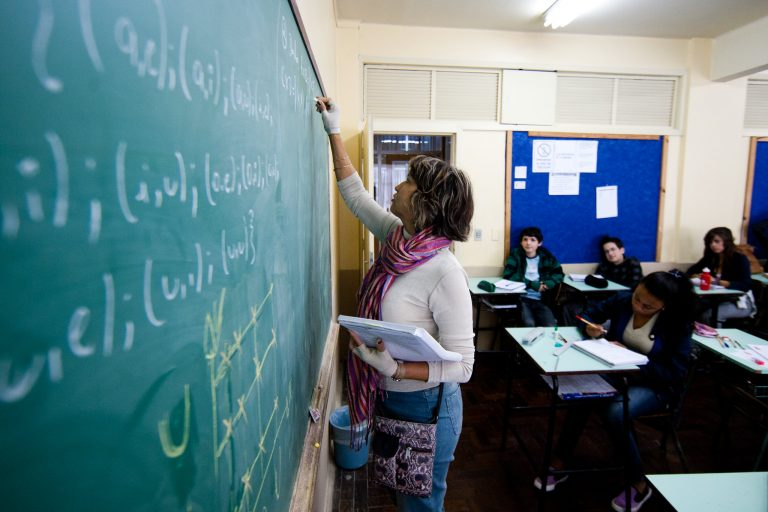 Professora escreve num quadro com giz, ao fundo os alunos estão sentados em carteiras