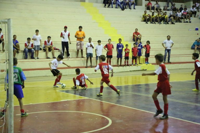 Meninos jogam futebol numa quadra coberta