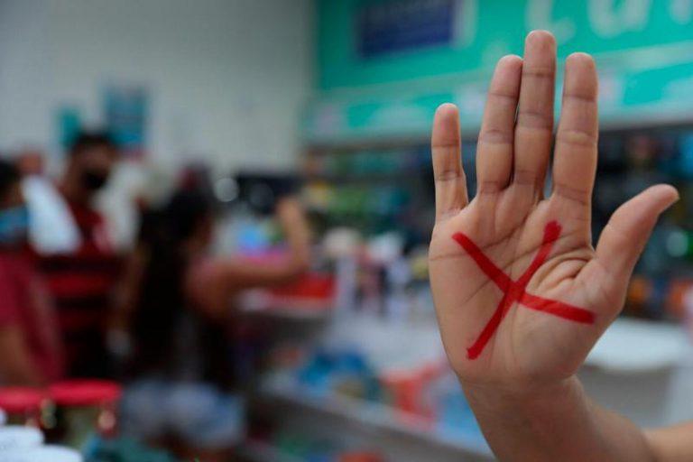 A mão de uma mulher está levantada e tem um X vermelho desenhado