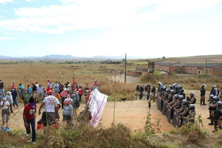 Moradores estão em frente a uma linha de policiais com escudos e capacetes numa operação de desocupação
