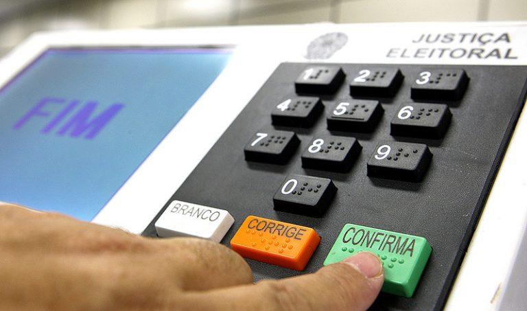 """Pessoa aperta a tecla onde está escrito """"Confirma"""" na urna eletrônica"""
