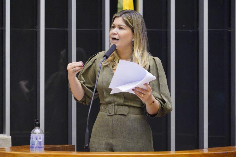 Deputada Aline Gurgel discursa no Plenário da Câmara. Ela é loira, usa um macacão cáqui e segura um papel