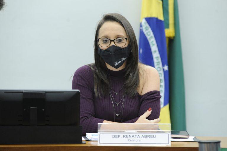Deputada Renata Abreu está sentada à frente de uma bandeira do Brasil. Ela veste uma blusa roxa e usa máscara