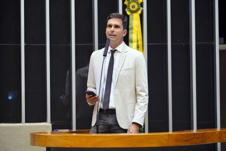 Deputado Luiz Lima discursa no Plenário da Câmara. Ele usa um terno claro e segura o celular