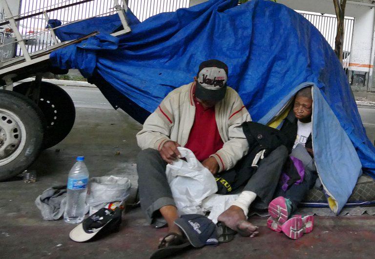Dois moradores de rua estão sentados à frente de uma barraca azul na calçada