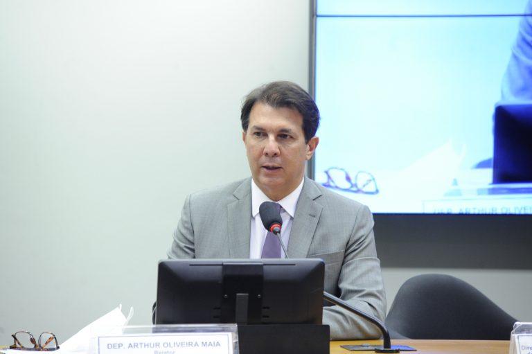 Deputado Arthur Oliveira Maia está sentado falando ao microfone