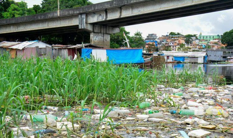 Moradias construídas a beira do rio e lixo