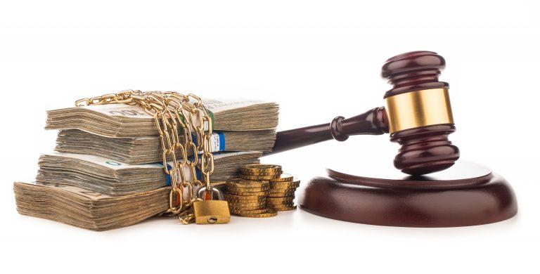 Uma pilha de notas de dinheiro está com correntes em volta. Ao lado há um martelo de juiz