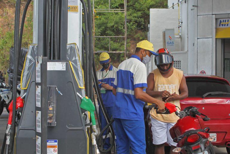 Motoqueiro abastece a moto em um posto de gasolina. Ele está em pé contando o dinheiro e o frentista segura a bomba junto à moto