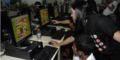 Professora mostrando informação para aluno no computador