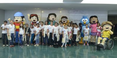 Crianças reunidas com os personagens do Plenarinho
